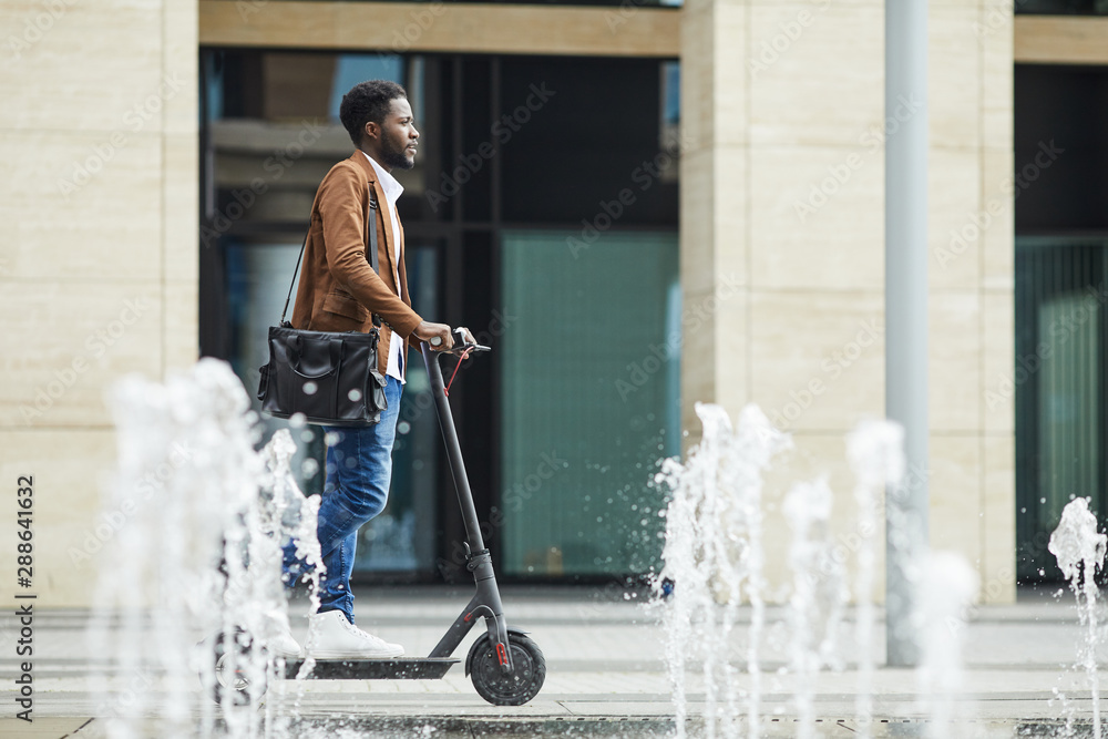 Fototapety, obrazy: Side view full length of modern African-American man riding electric scooter through fountain while commuting to work in city, copy space