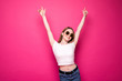 canvas print picture - Young pretty woman with raised hands isolated on pink background