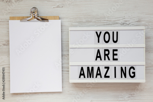 Pinturas sobre lienzo  'You are amazing' words on a modern board, clipboard with blank sheet of paper on a white wooden background, overhead view