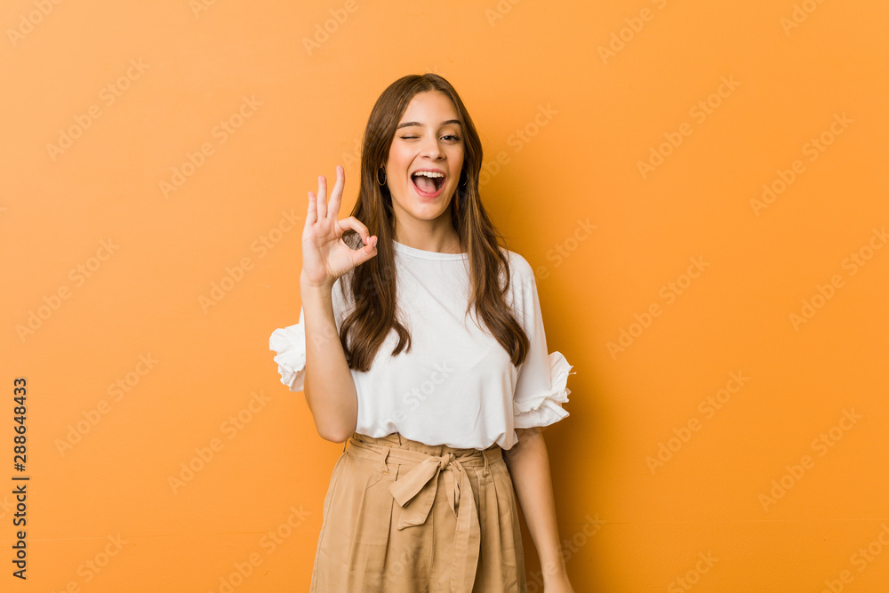 Fototapety, obrazy: Young caucasian woman winks an eye and holds an okay gesture with hand.