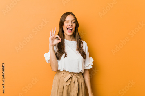 Fotografie, Obraz  Young caucasian woman winks an eye and holds an okay gesture with hand