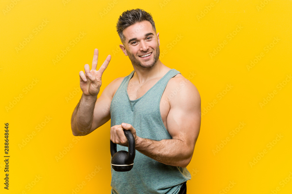 Fototapeta Caucasian man holding a bumbbell showing victory sign and smiling broadly.