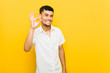 Young hispanic man cheerful and confident showing ok gesture.