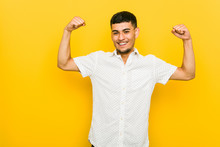 Young Hispanic Man Showing Strength Gesture With Arms, Symbol Of Feminine Power