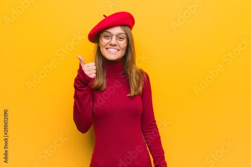Valokuva  Young french artist woman smiling and raising thumb up