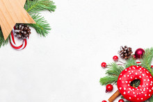 Christmas Background Border Composition With Donut, Green Xmas Fir Branch, Red Holly Berries And Baubles On White Background