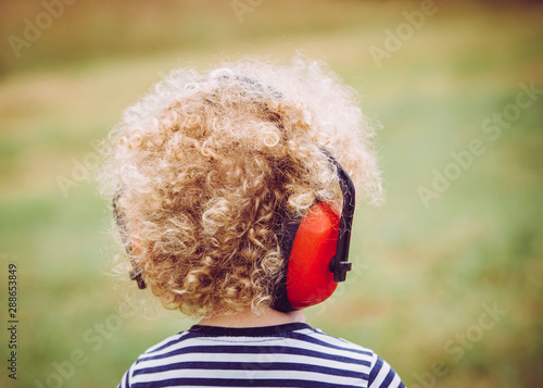Young child wearing noise blocking headphones at outdoor concert, preventing hearing loss at young age concept Fototapet