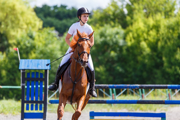 Young girl riding horse on equestrian sport show