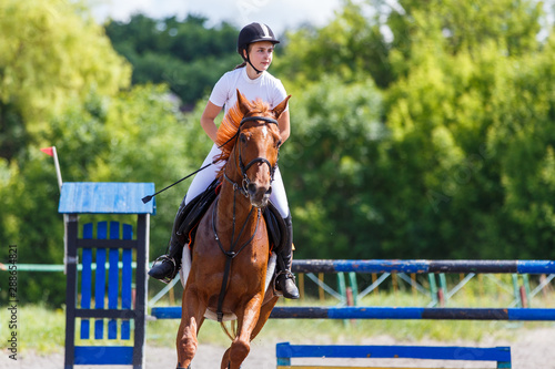 Fototapeta Young girl riding horse on equestrian sport show obraz