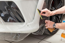 Retrofitting The Car With A Solid Transparent Protective Film, The Master Smooths The Surface By Squeezing Air Bubbles With A Scraper, Protecting The Vehicles From Scratches And Chips In The Workshop