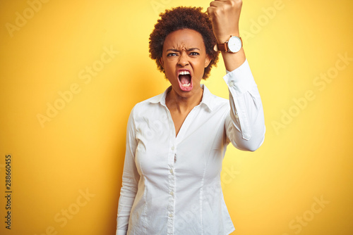 Fototapeta  African american business woman over isolated yellow background angry and mad raising fist frustrated and furious while shouting with anger