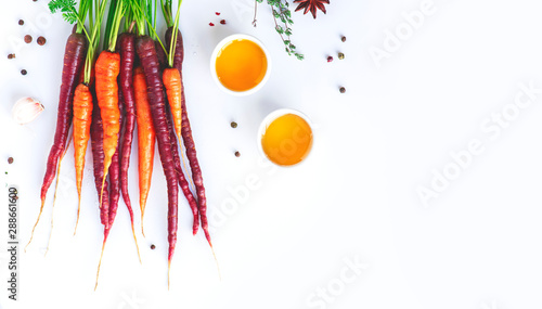 Carta da parati Orange and purple carrots, honey, oil and spices on a white background, top view, copy space