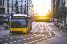 Yellow Public Transportation Bus Passing By The City Of Berlin Germany
