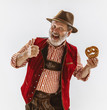 canvas print picture - Portrait of Oktoberfest senior man in hat, wearing the traditional Bavarian clothes. Male full-length shot at studio on white background. The celebration, holidays, festival concept. Eating puff.