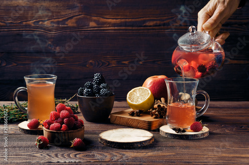 Recess Fitting Tea Pouring fruit tea with raspberries, bramble, apple and lemon in cup from teapot