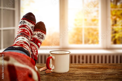Autumn window and woman legs with socks. Free space for your decoration.