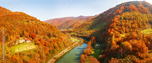 Stampa su Tela  Mountain river flows in autumn colored valley