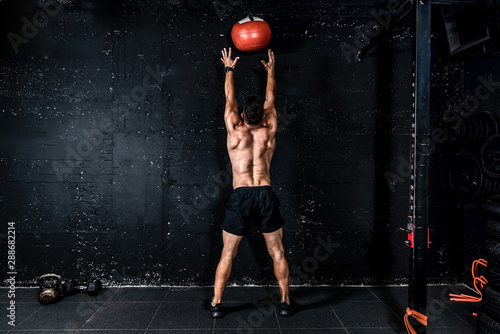 Valokuvatapetti Young strong sweaty focused fit muscular man with big muscles doing throwing med