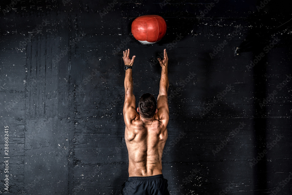 Fototapety, obrazy: Young strong sweaty focused fit muscular man with big muscles doing throwing medicine ball up on the wall for training hard core workout in the gym real people selective focus