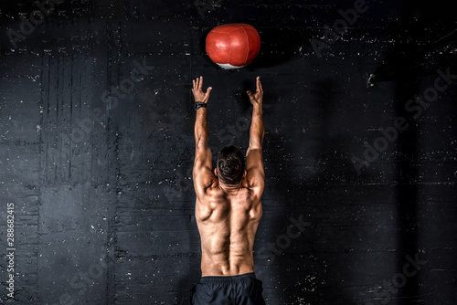 Fotografia  Young strong sweaty focused fit muscular man with big muscles doing throwing med