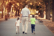 Grandfather With Two Kids Walk...