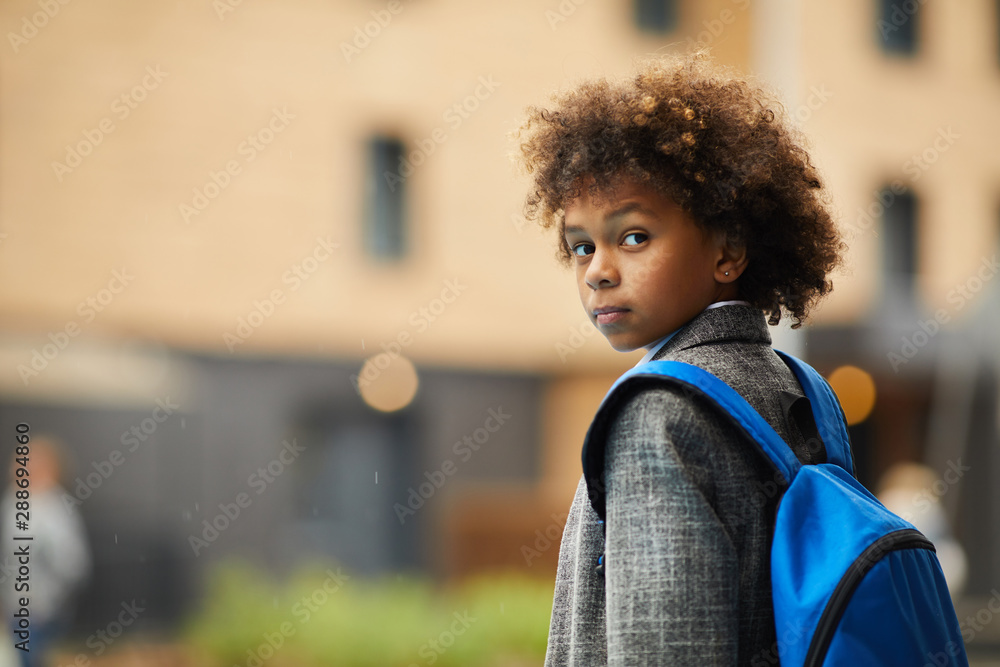 Fototapeta Portrait of African schoolboy with curly hair and with backpack behind his back looking at camera while going to school