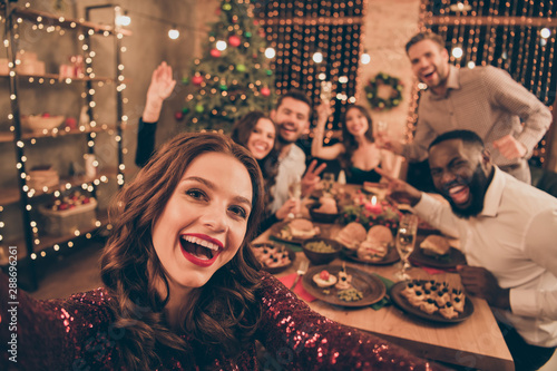 Close up photo of cheerful fellows in formal wear sit around table enjoy christmas party x-mas holidays making selfie in house full of noel decoration