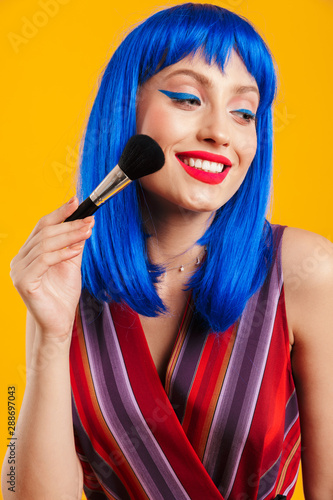Photo  Portrait of cheerful beautiful woman wearing blue wig looking aside and applying