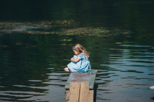 Thoughtful Child Is Sitting On A Small Wooden Pier On The Background Of The River