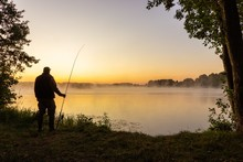 Silhouette Of Angler Standing On The Shore Of The Lake During Sunrise