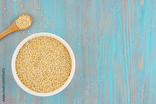 Valokuvatapetti quinoa seed grain in white bowl with spoon on wooden blue table