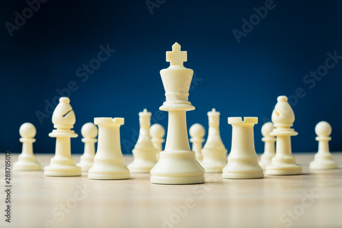 La pose en embrasure Fleur White chess pieces with king in front placed on wooden desk