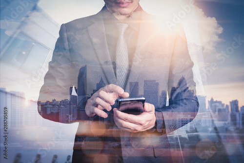 Fotografie, Obraz  The double exposure image of the business man using a smartphone during sunrise overlay with cityscape image