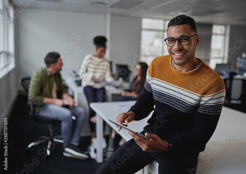 Portrait of a successful smiling businessman holding digital tablet looking at camera sitting in front of team at modern office