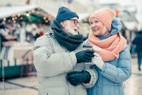 Fototapeta Elderly couple clanging cups of coffee and smiling