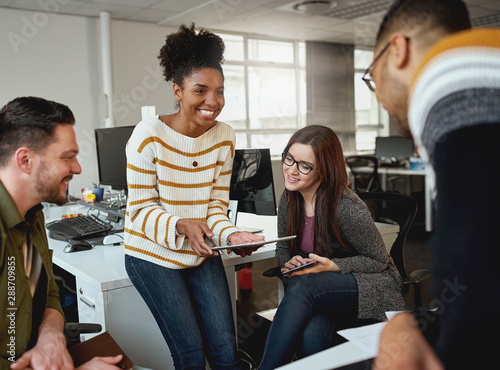 Creative young woman showing business plan on digital tablet to colleagues during a meeting in front of business group - start up company