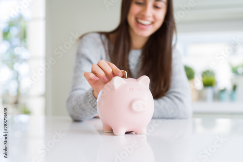 Fotografía  Young woman smiling putting a coin inside piggy bank as savings for investment