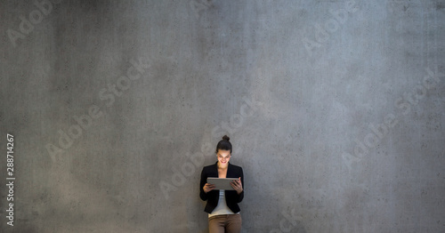 Obraz Young business woman with tablet standing against concrete wall in office. - fototapety do salonu