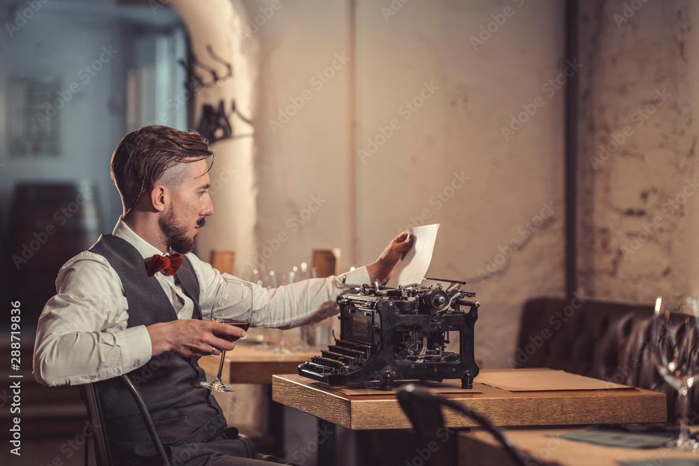 Fototapeta Young man with a retro typewriter