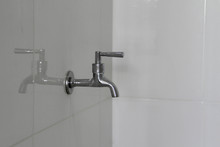 Stanless Steel Water Tap On White Wall In The Bathroom.