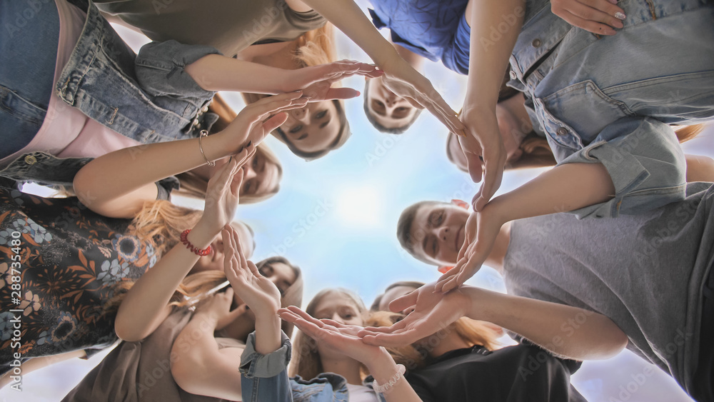 Fototapety, obrazy: Young people putting their hands in circle on sky background. Unity concept.