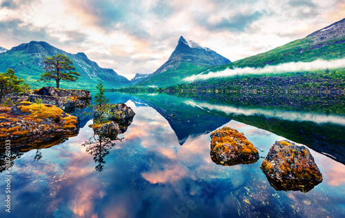 Unbelievable summer sunrise on Innerdalsvatna lake. Colorful morning scene in Norway, Europe. Beauty of nature concept background. Artistic style post processed photo. Orton Effect..