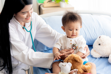 Asian female doctor is using a stethoscope Listen to heart rate Of a 1 year old patient who came to treat the flu, which is pandemic, to health care and children concept.