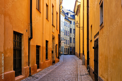 Fototapeten Bright yellow buildings on a narrow cobblestone street in Gamla Stan, the Old Town of Stockholm, Sweden