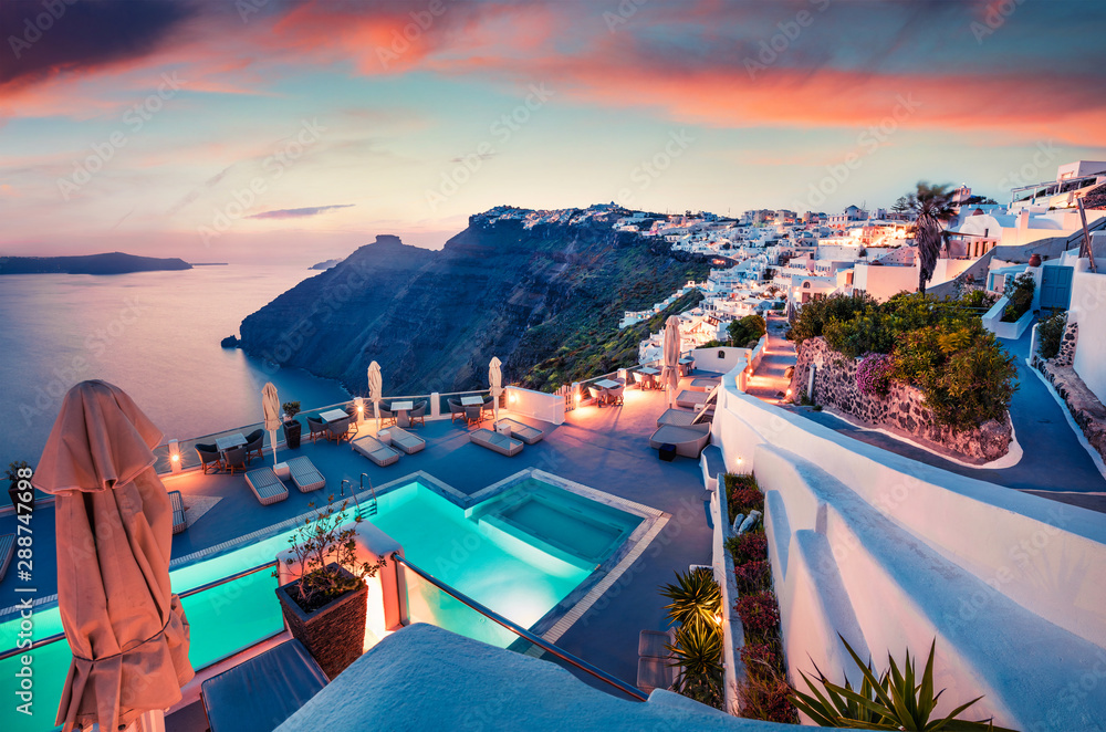 Fototapeta Fantastic evening view of Santorini island. Picturesque spring sunset on famous Greek resort Fira, Greece, Europe. Traveling concept background. Artistic style post processed photo.