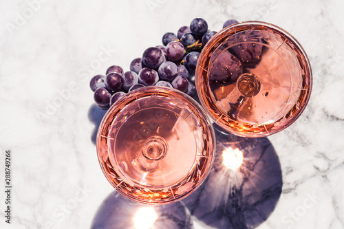 Foto Two crystal stemmed glasses with rose wine on marble table outdoors in a cafe
