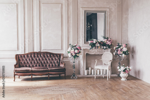 Vintage interior sofa with a vase of flowers in shabby chic style.