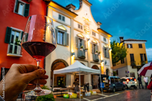 hand holding a glass of red wine in the town of Neive, Italy, one of the main villages of the Langhe hills, famous district of Barolo and Barbaresco wine Canvas Print