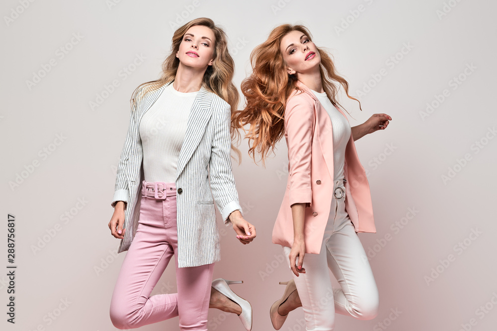 Fototapeta Fashionable autumn woman dance having fun with stylish hairstyle, fall makeup. Two Excited funny Girl, Trendy coral pink outfit, fashion wavy hair. Gorgeous female model, autumnal dancing concept