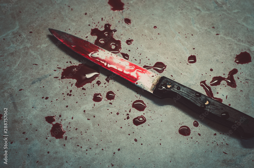Fototapeta Bloody knife lies on a light background with dark red drops